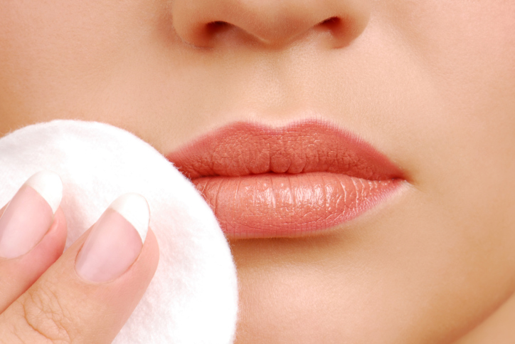 Ñleaning woman face with cotton pads. Lips close-up
