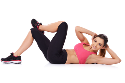 Beautiful young woman doing exercises on the floor to strengthen her muscles, studio portrait on white