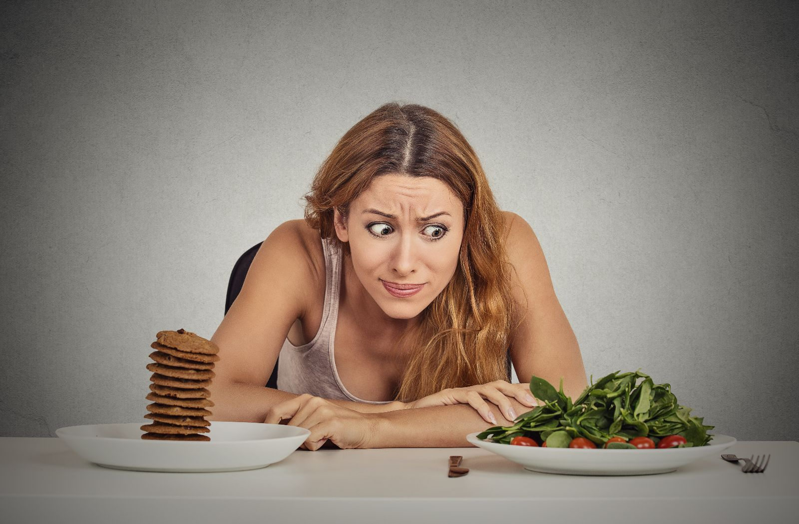 Portrait young woman deciding whether to eat healthy food or sweet cookies she is craving sitting at table isolated grey wall background. Human face expression emotion reaction Diet nutrition concept